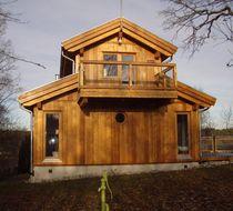 Maison préfabriquée / classique / en bois massif / avec terrasse