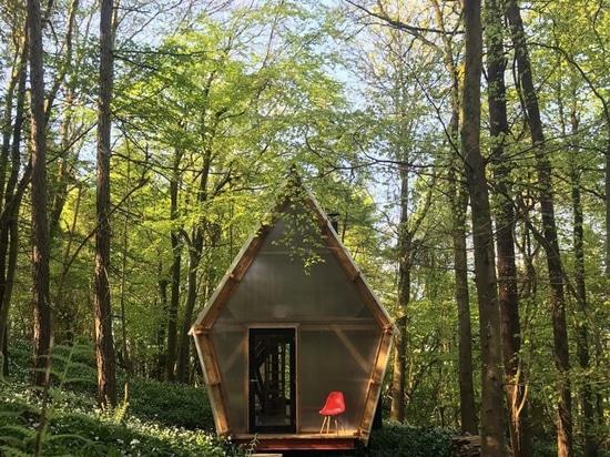 le studio invisible établit le coût bas, la maison réadressable utilisant le bois de construction et les matériaux jetés