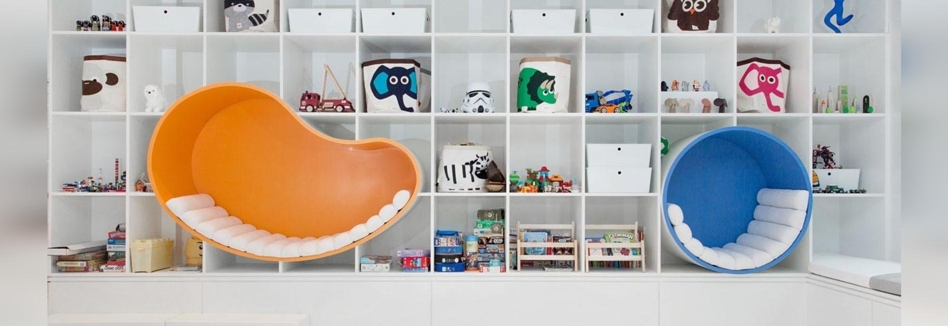 Des coins pour s'asseoir ont été intégrés à un mur d'étagères dans cette salle de jeux pour enfants
