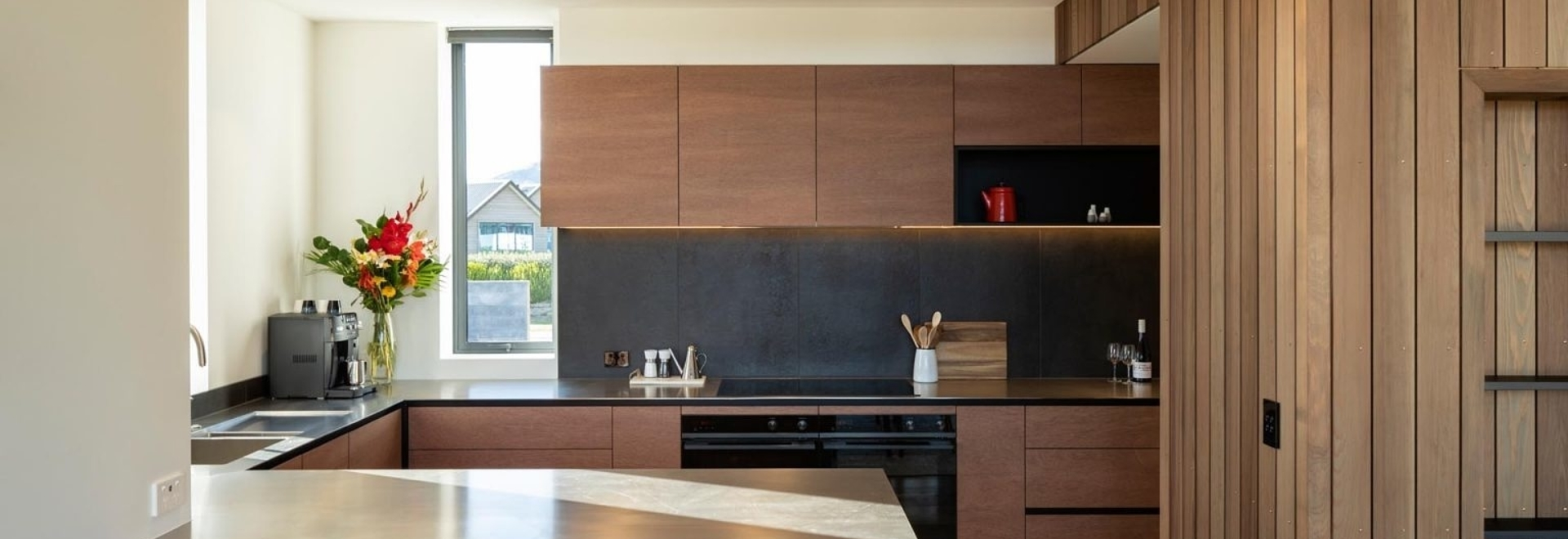 Le revêtement en bois vertical foncé de l'extérieur de cette maison moderne lui confère une forte personnalité