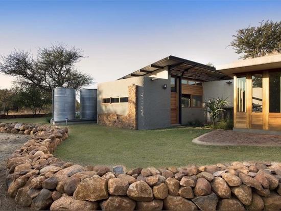 La maison énergie-futée terreuse maintient une eco-empreinte de pas minimale dans le buisson sud-africain