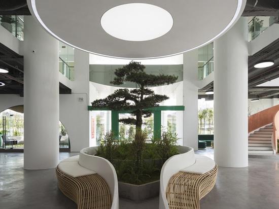 Un escalier couleur cuivre et des mini-bambous fournissent un intérieur tropical pour ce bureau au Vietnam