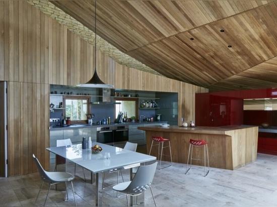 Une maison en pierre à toit vert s'élève dans un paysage rural anglais