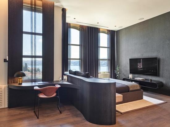 La tête de lit se transforme en bureau pour créer un petit bureau à domicile dans cette chambre