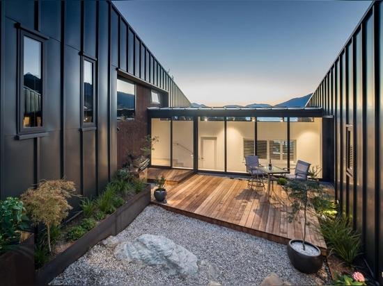 Cette maison à flanc de colline avec un revêtement métallique noir a été conçue pour maximiser la vue sur le lac