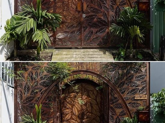 Des écrans métalliques avec un motif de feuille ornent l'intérieur et l'extérieur de cette maison