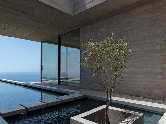 Une longue et mince piscine s'étend de cette maison à flanc de colline